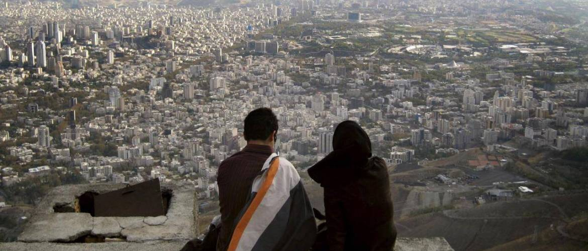 File photo of an Iranian couple sitting, overlooking the city of Tehran
