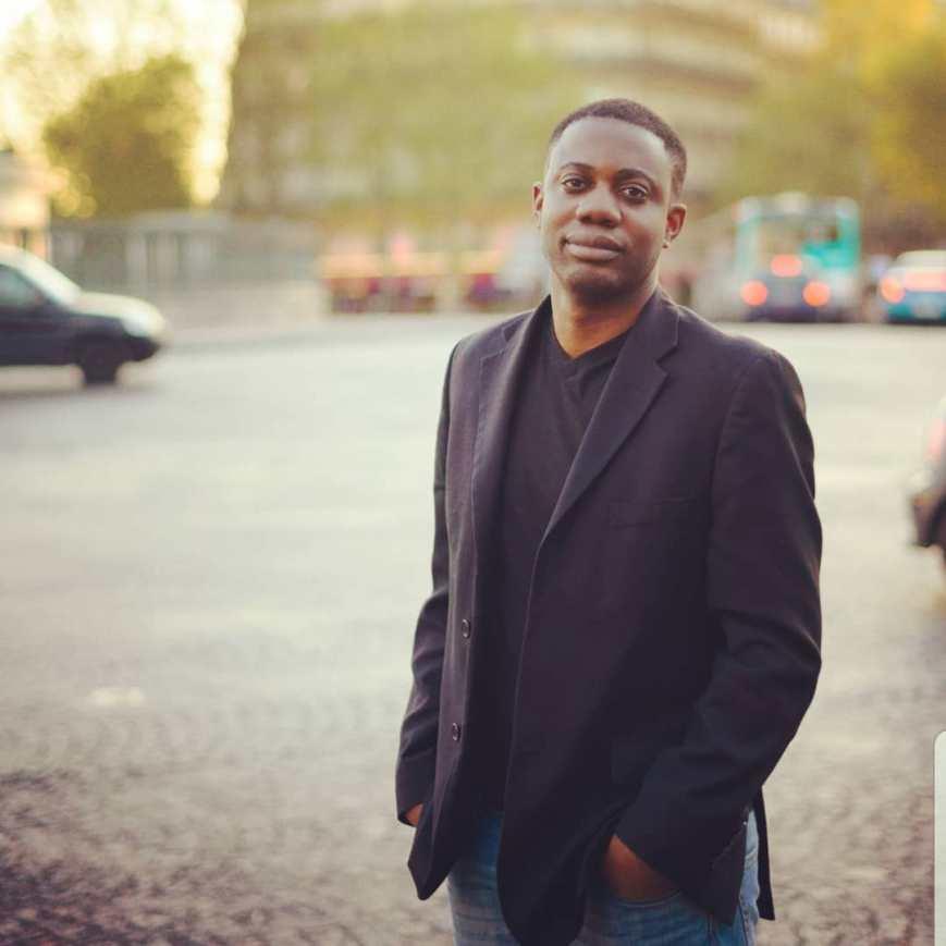 Kahi Lumumba, veste noire, jean bleu, mains dans les poches