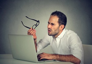 an employee looking confused at his computer screen