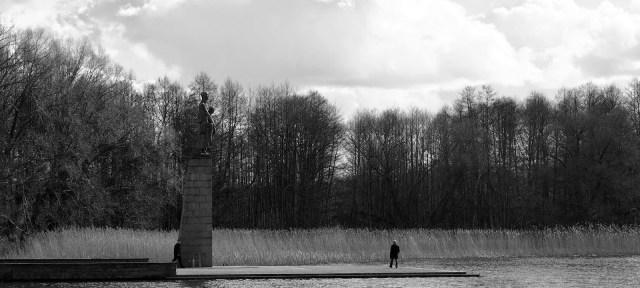 Eine Statue hoch oben auf einem Sockel im See zur Erinnerung an das KZ Ravensbrück