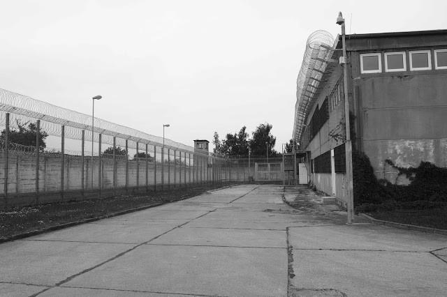 Blick entlang einer der Werkhallen. Zwar ist der Stacheldraht und erster Zaun neu, doch ist dieser an alter Stelle. Zwischen Zaun und Mauer liefen die Hunde. Der Wachturm in Hintergrund ist nicht mehr in Nutzung.