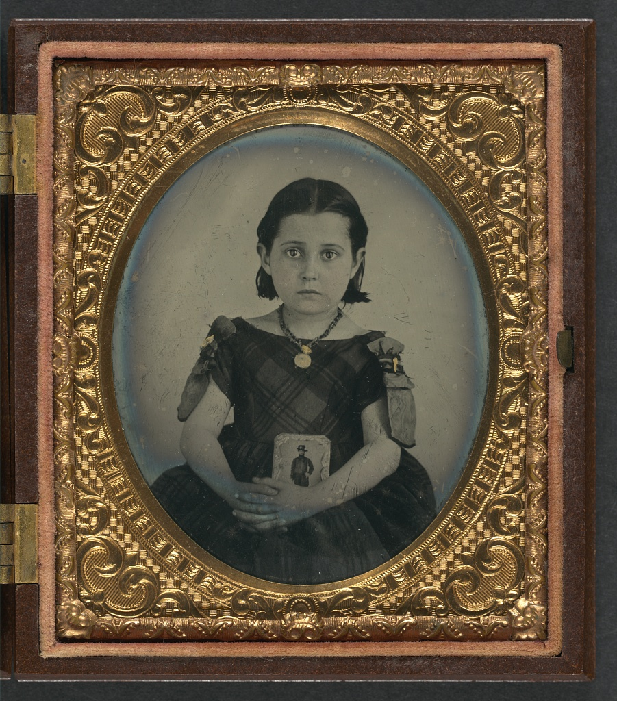 A girl in mourning clothes holds an image of her father during the Civil War (Library of Congress)