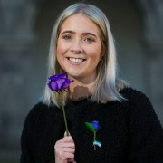 Aoife Rafter poses with a purple rose to mark 65 Roses Day