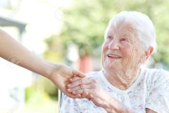 14396894-Happy-senior-woman-holding-hands-with-caretaker-Stock-Photo-elderly-people-old