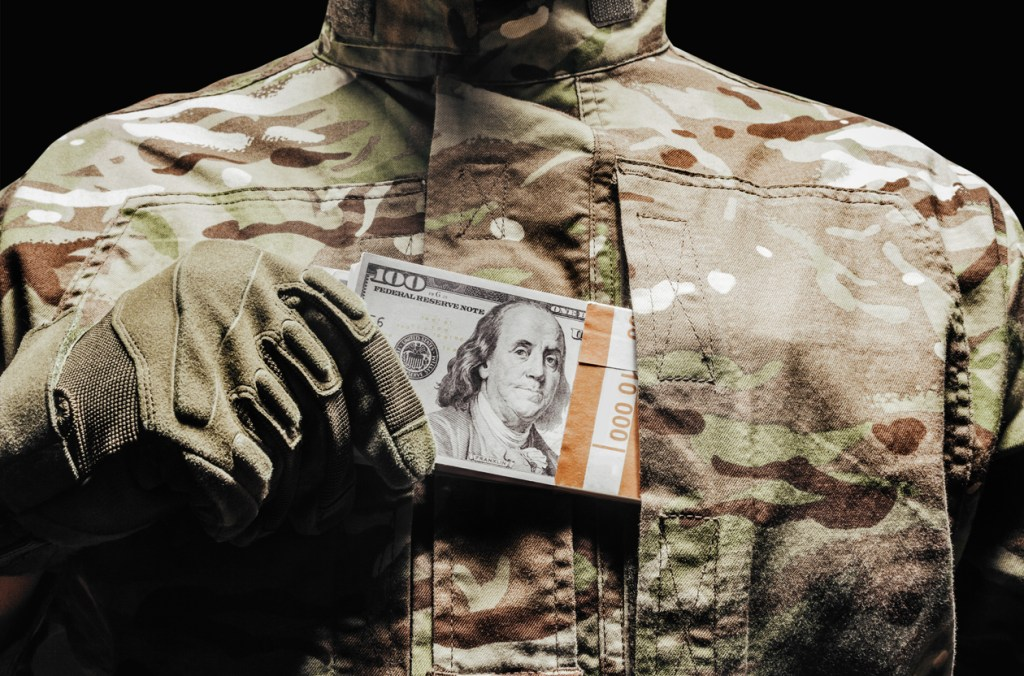 Photo of a soldier in camouflage and tactical gloves putting money in pocket.