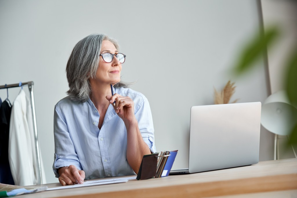 Inspired mature grey-haired woman fashion designer thinking on new creative ideas at workplace. Smiling beautiful elegant classy middle aged older lady small business owner dreaming in atelier studio.