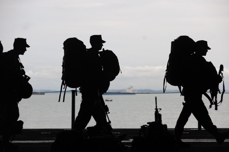 Silhouetted soldiers departing with gear