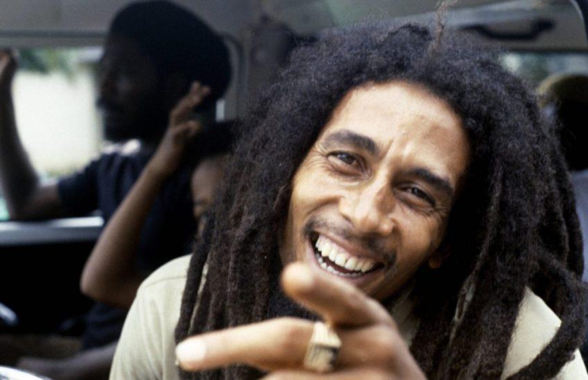 Bob Marley sorrindo, feliz, e apontando para a câmera, quebrando a quarta parede.