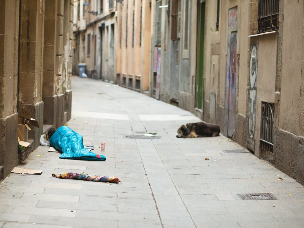 homeless person in blue sleeping bag