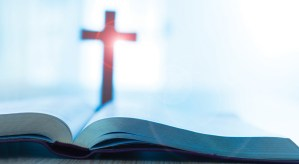 Bible and cross on desk.