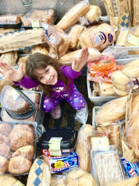 young volunteer in basket of donated bakery items from Tom Thumb