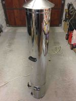 Fabric steamer showing cylindrical steel chamber on top of the water heater