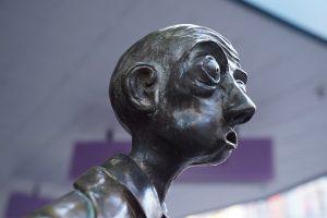 Une statue d'un homme, bouche ouverte, sans mot