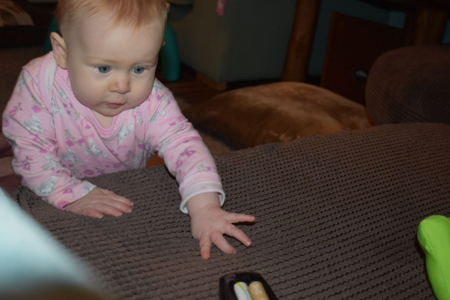 Baby reaching for a remote whilst standing