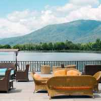 terrace with furniture against lake and green mountain