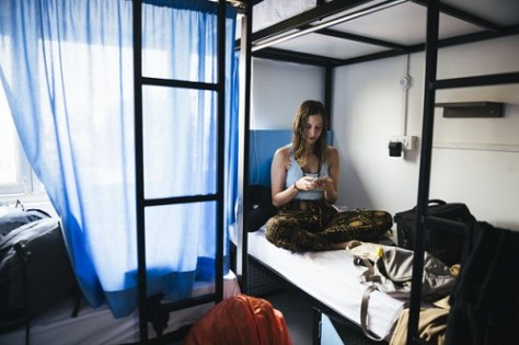 Girl using her phone and sitting in an on-campus accommodation in a university