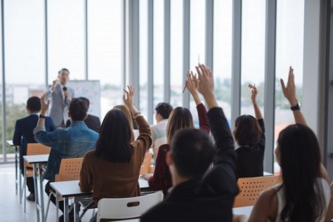 Students studying in Australia raising their hands