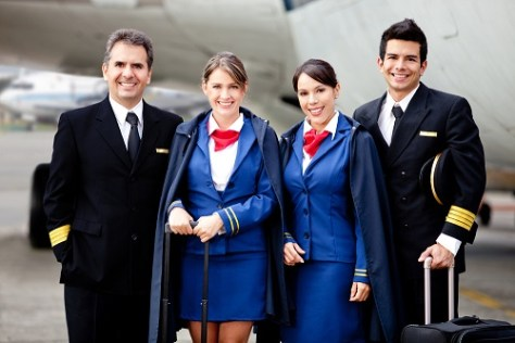 Airline captain and cabin crew standing near the plane