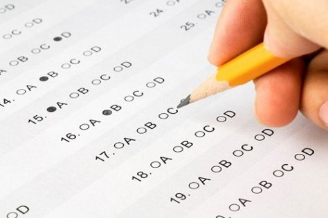 Student filling an answer sheet with a pencil