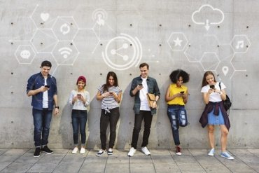 Diverse people using their phones and networking while studying abroad