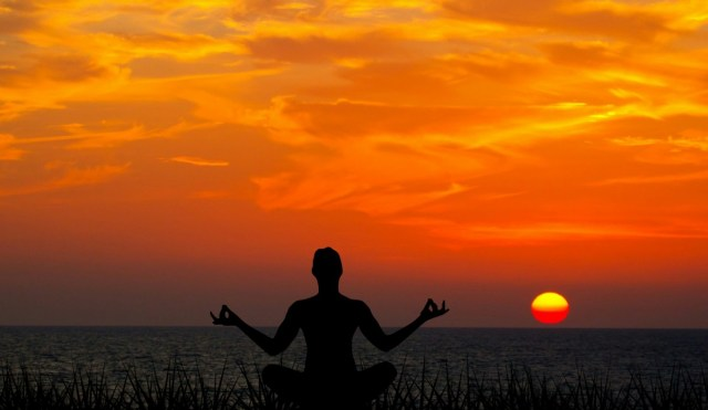 person meditating in front of sunset