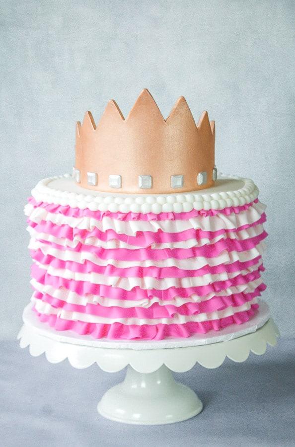 Gold Gumpaste crown on top of ruffled cake