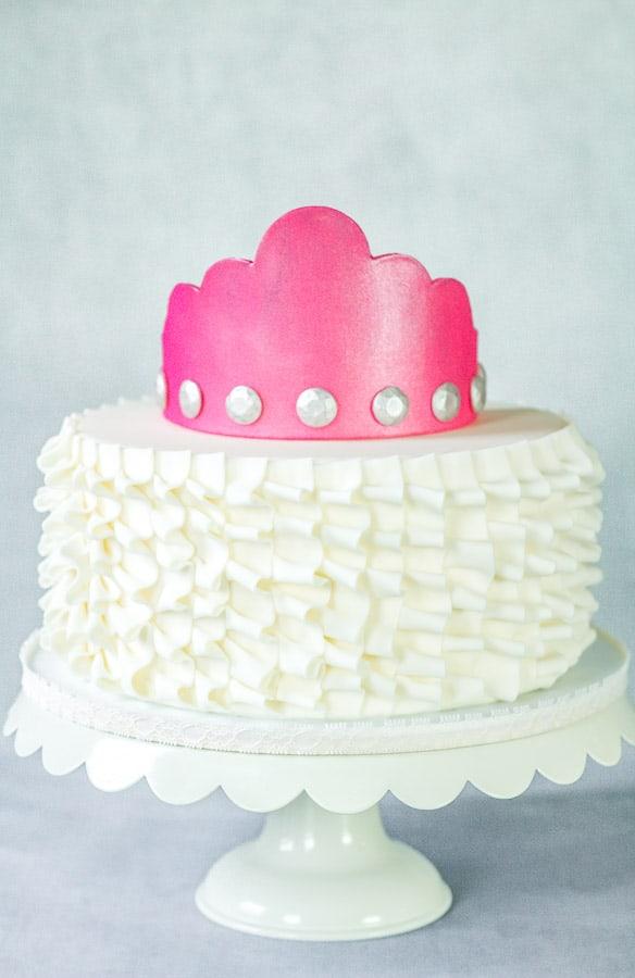 Hot pink gumpaste crown on top of ruffle cake