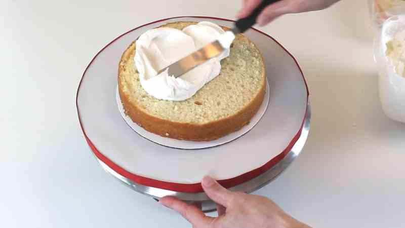 Adding buttercream filling to cake