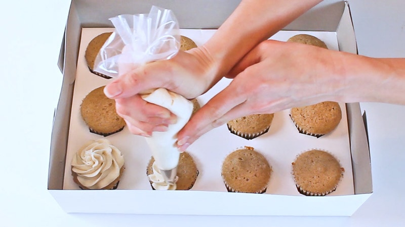 piping onto cupcakes in a box