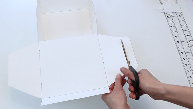 cutting the lid flaps of the posterboard treat box