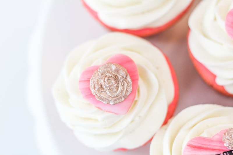 close up of valentine's cupcake topper with gold fondant rose