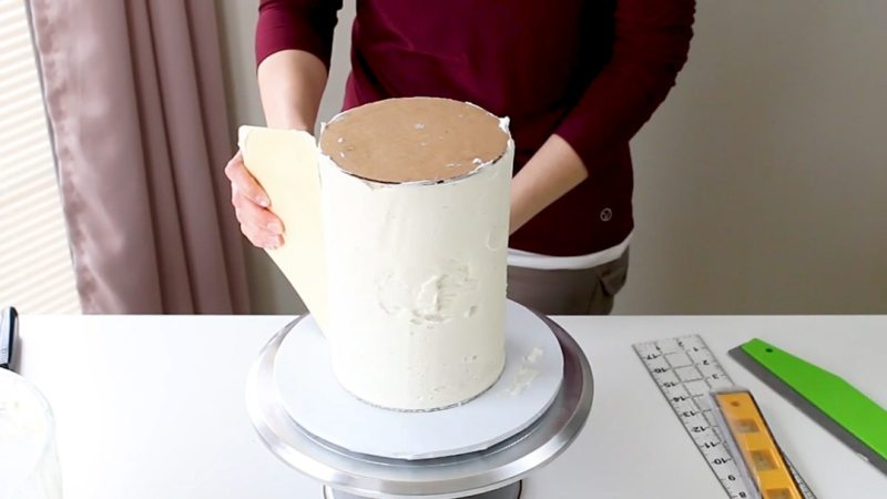 Smoothing buttercream on tall cake