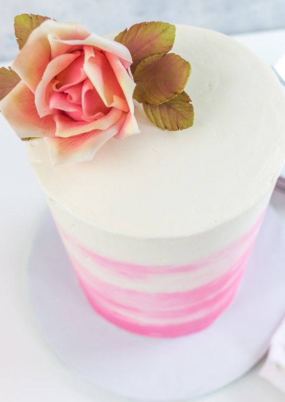 Adding a flower to a tall cake