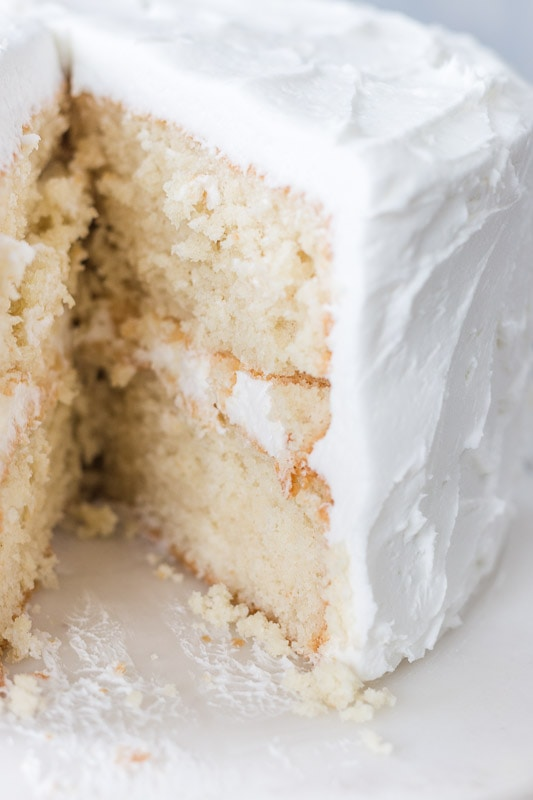 Cut moist white cake on a cake stand
