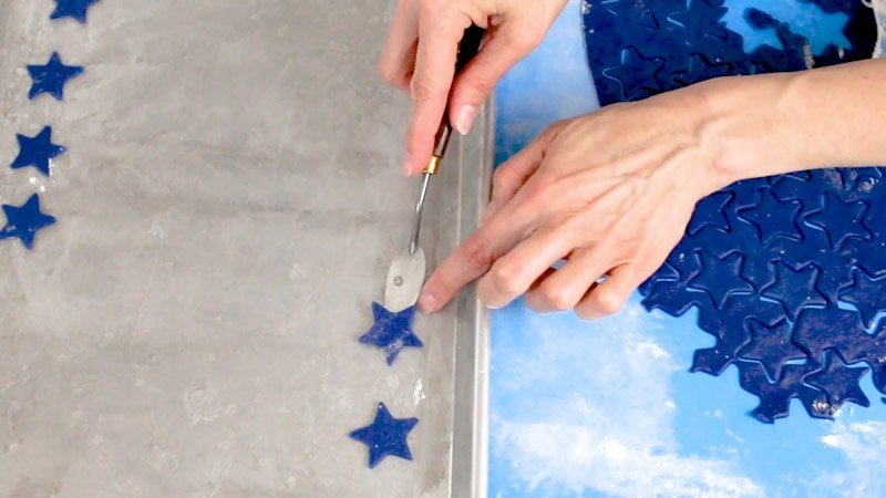 Placing blue star cookie dough onto cookie pan