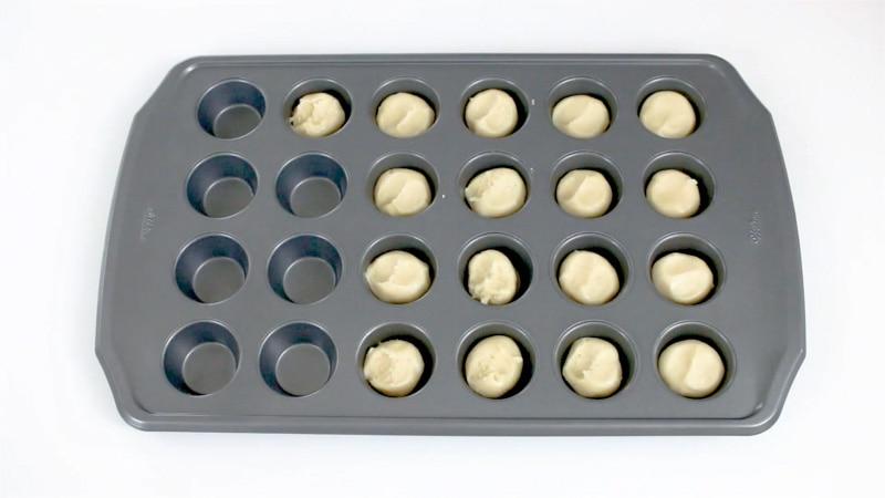 Adding cookie dough to mini muffin pan