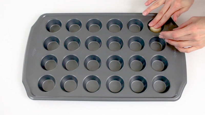 Adding cookie dough to mini muffin pan to make cookie cups