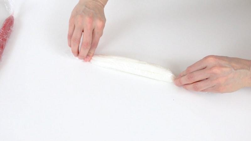 Rolling up white buttercream in saran wrap