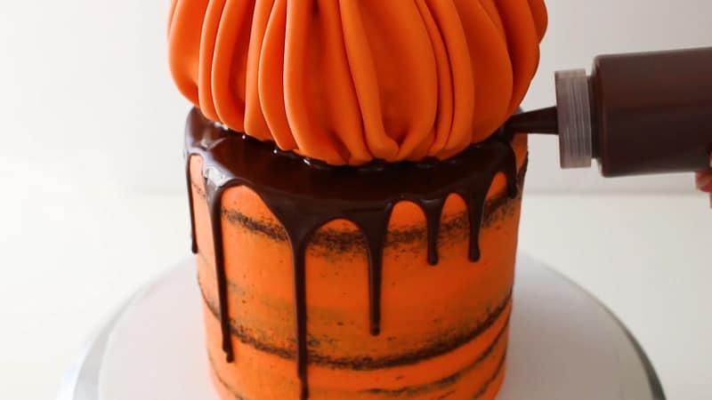 adding drip ganache to the cake