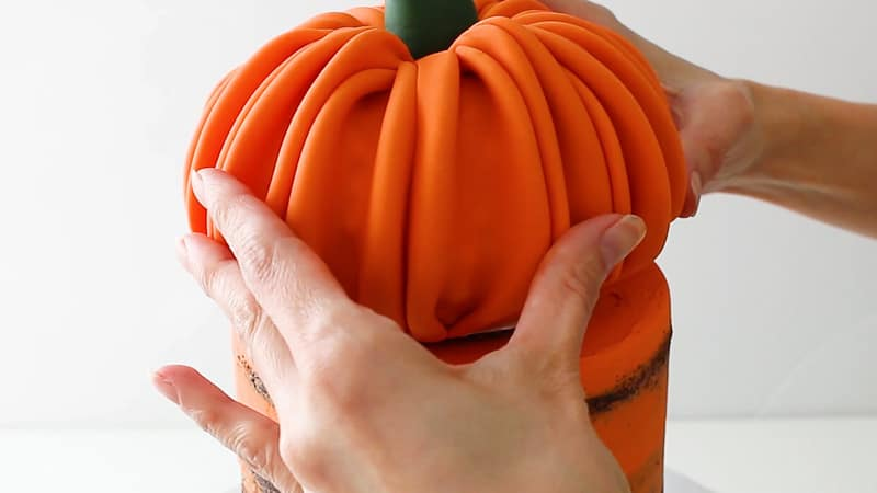 adding the pumpkin cake topper