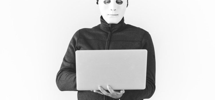 Person with mask holding laptop computer