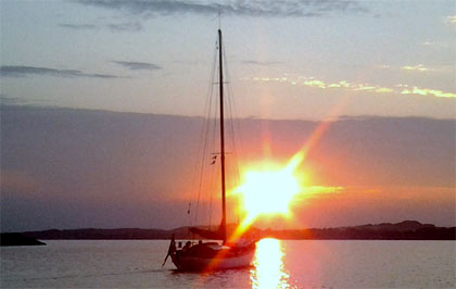 Foto af sejlbåd som sejler ud i solnedgangen