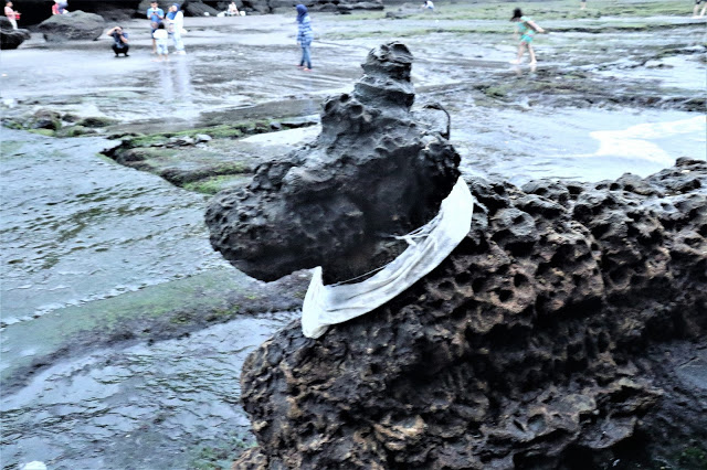 Eroding away slowly - sculpture of lion at entrance to Tanah Lot temple