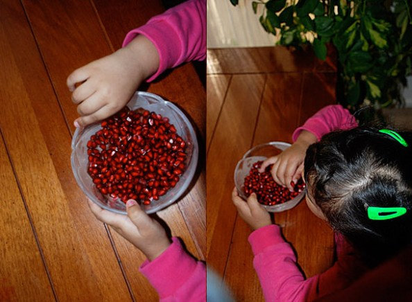 Li'l Z can't take her hands off the pomegranate!