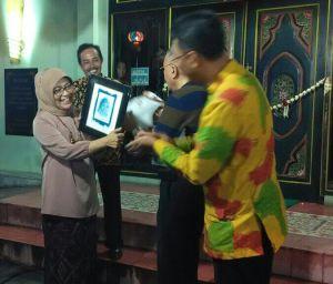 Prof. Drs. Soeprapto Soedjono, M.F.A., Ph.D. didampingi Dekan FSMR ISI Yogyakarta memberikan cindera mata foto diri cetak old print kepada Dra. Watie Moerany, M.Hum.