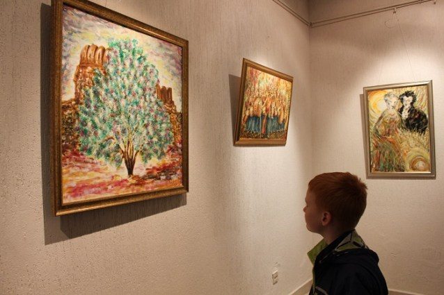 A child looks at paintings by Russian diplomat Mr. Youri Kozlov at COMSATS Art Gallery in Islamabad. Photo by Sana Jamal