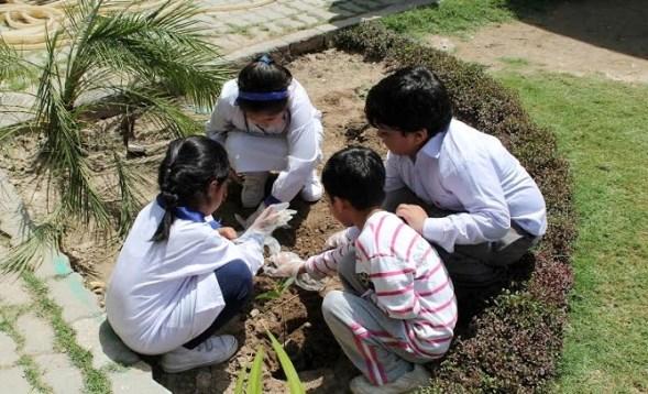 Children planting saplings on Earth Day 2016