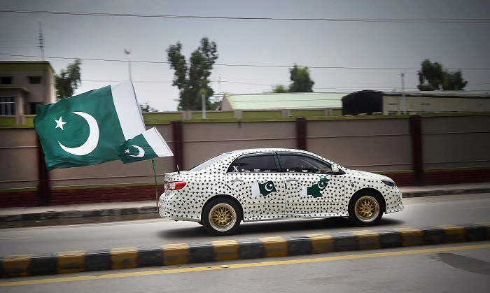 A Pakistani drives his car decorated with national flags to mark the country's Independence Day in Peshawar on August 14, 2017. AFP Photo/Abdul Majeed