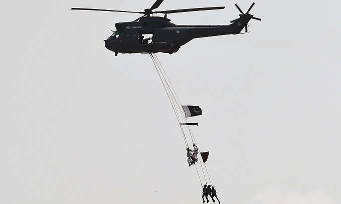 Pakistani soldiers hang from a helicopter performing a fly-past at the air show held in Islamabad on 70th Independence day