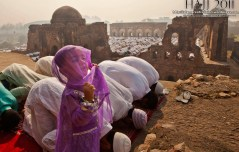 A young Indian Muslim girl gestures as others offer prayers during Eid al-Adha in New Delhi, India on November 7, 2011.